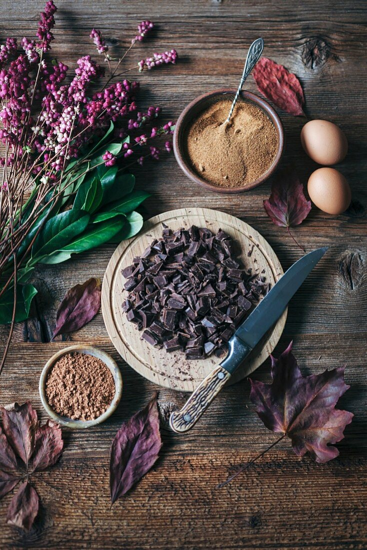 Chopped chocolate, coconut sugar, eggs and cacao powder on wooden table