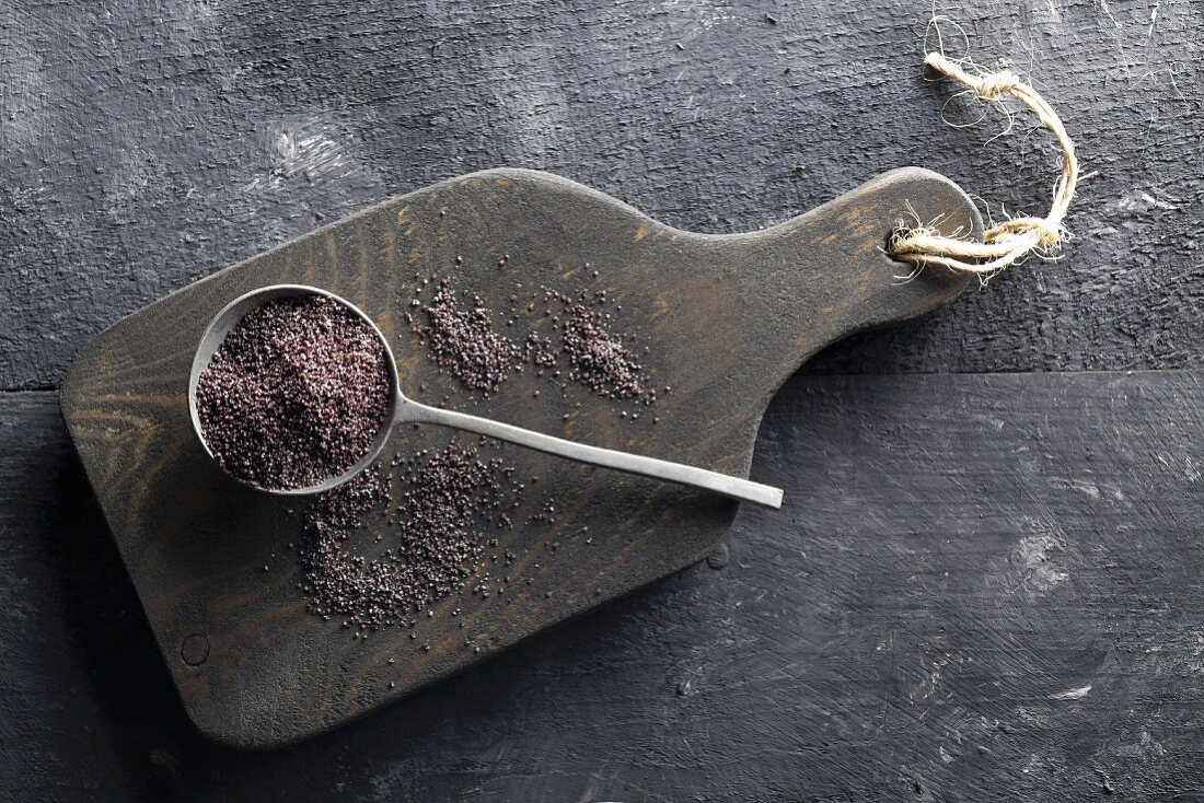 Poppy seeds on a spoon on a wooden board with a black background