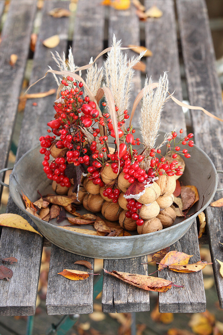 A centrepiece made of walnuts, reeds and red berries