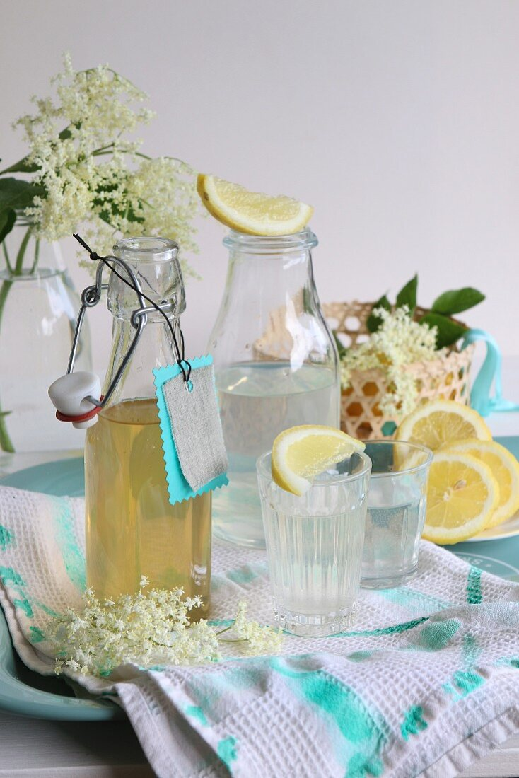 Elderflower blossom syrup in a bottle and poured into glasses with lemon slices