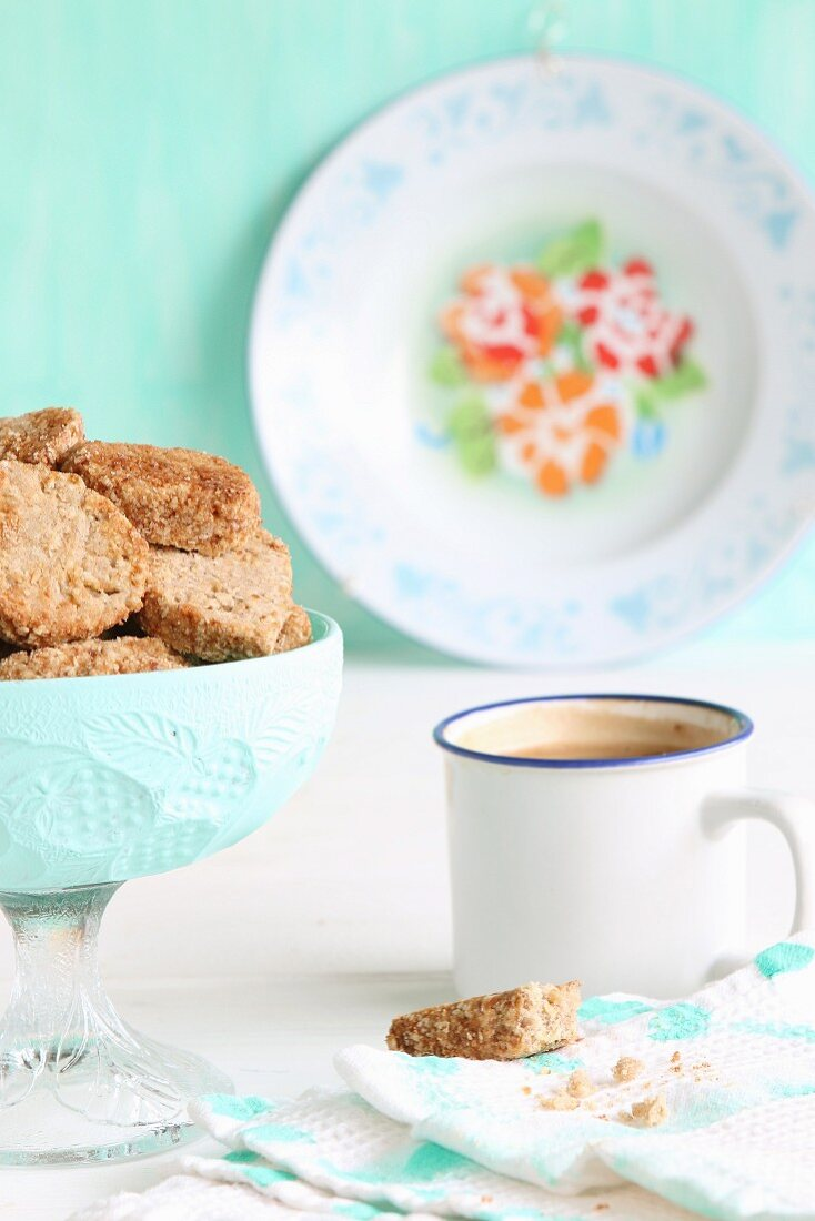 A bowl of gluten-free biscuits with buckwheat flour and coconut blossom sugar, and coffee in an enamel cup
