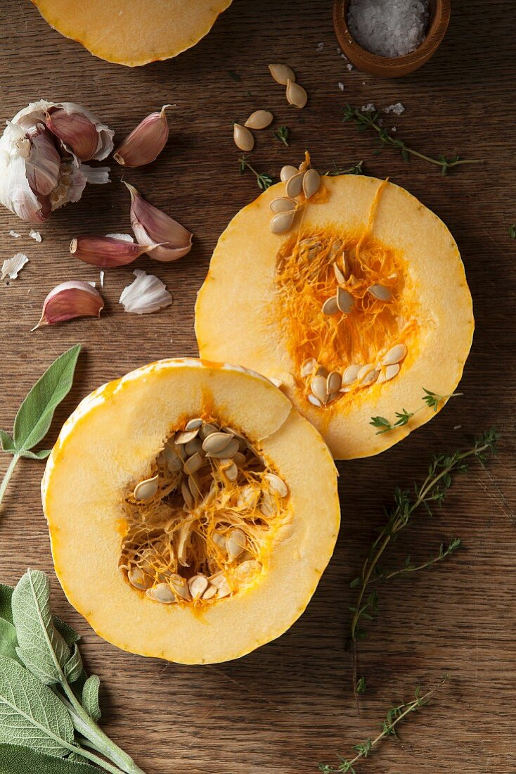 A halved munchkin pumpkin with garlic, sage and thyme on a wooden background