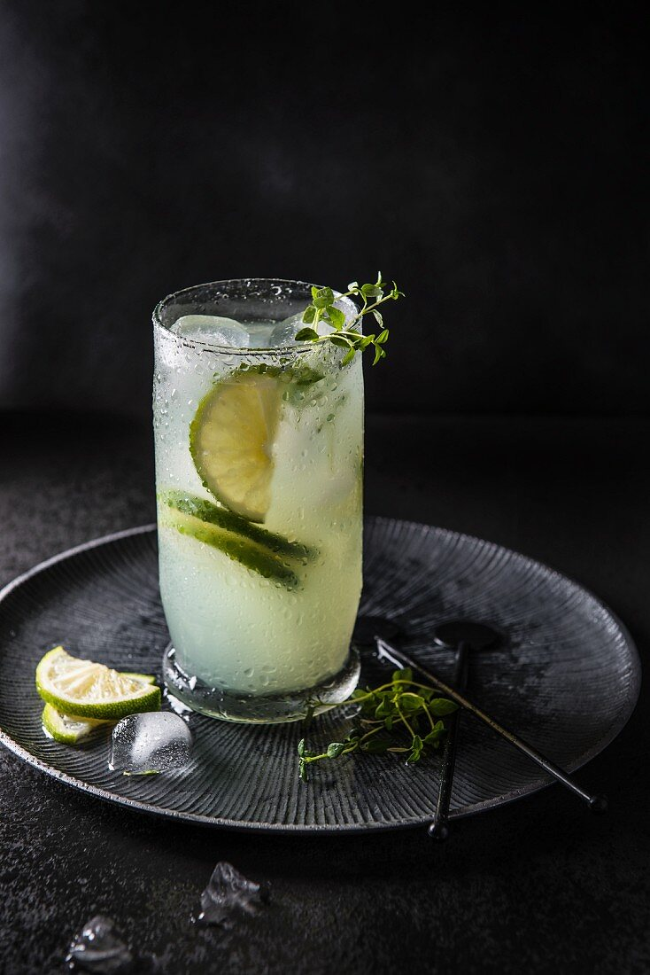 A cocktail made with bitter lemon, lime and gin on ice, garnished with thyme