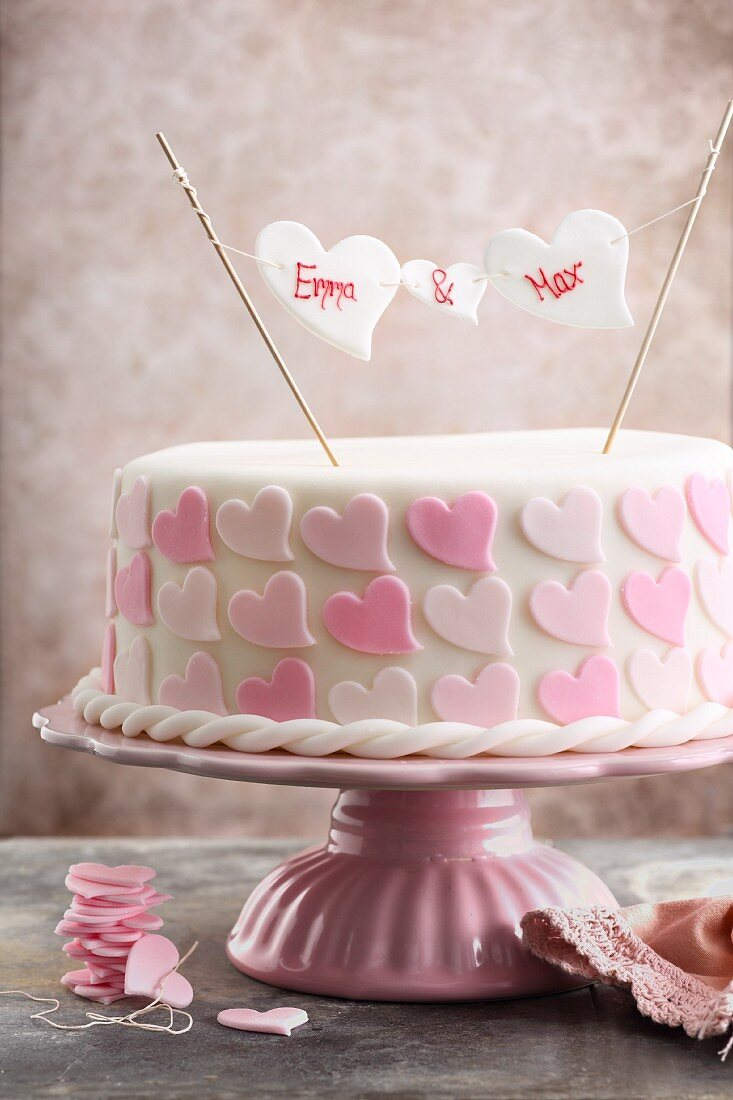 A romantic pink 'Will you...' cake with icing hearts