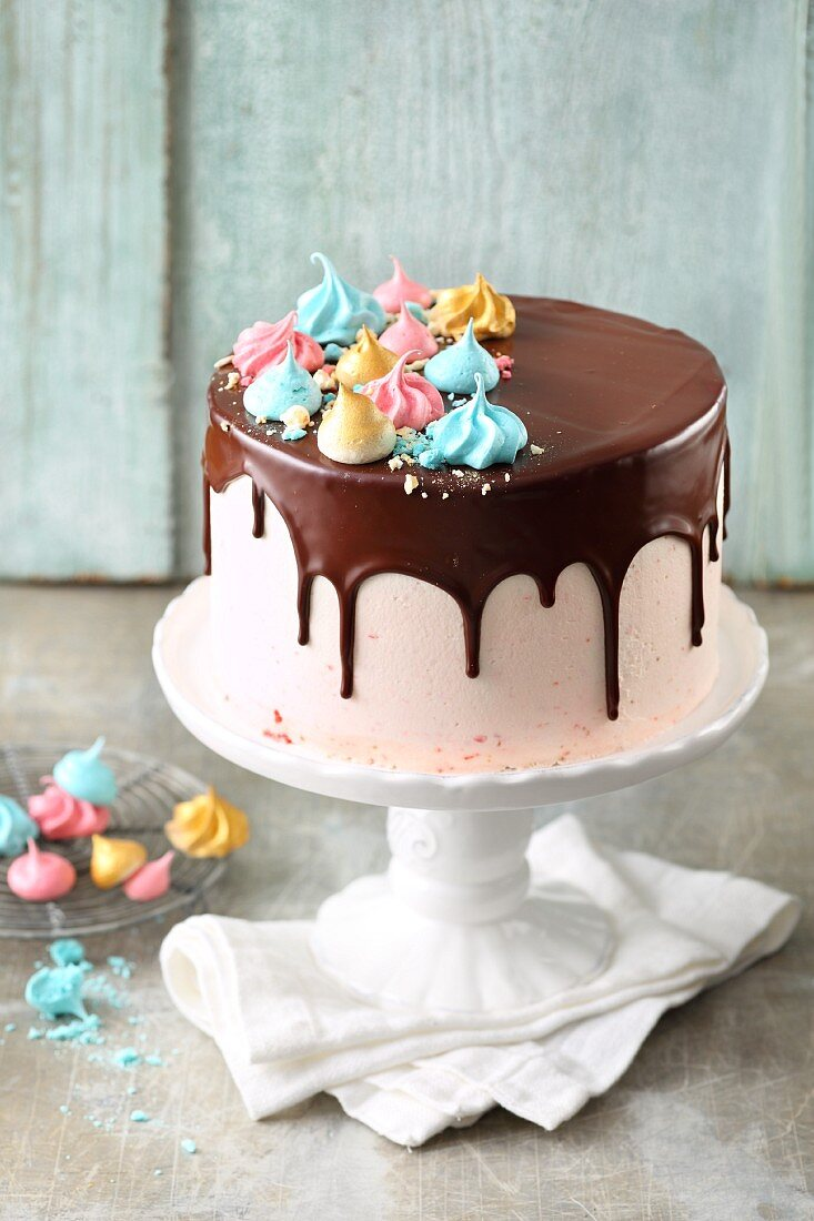 Strawberry buttercream cake with chocolate glaze and colourful meringue dots
