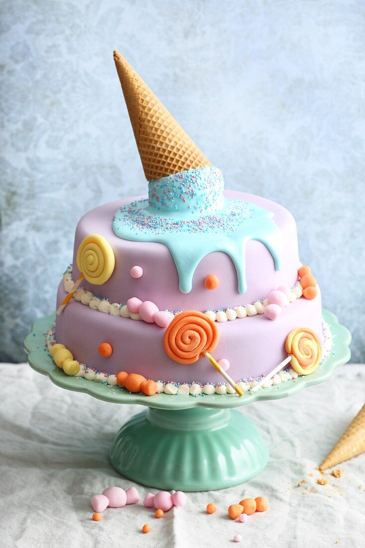 Brightly coloured fondant 'Candy Cake' decorated with lollies and melting ice cream from a cone