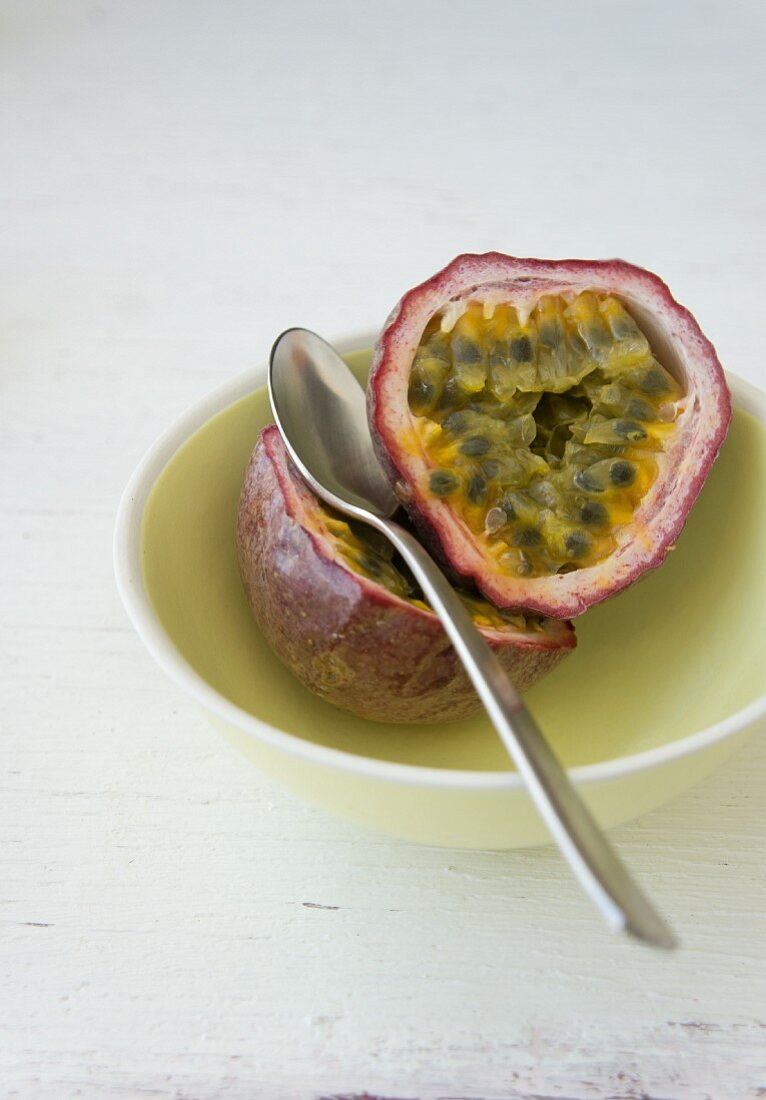 Passion fruit, halved, in a bowl with a spoon