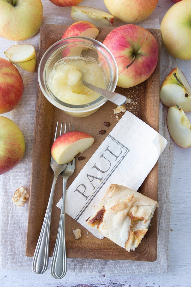 A serviette printed with a name, cutlery, apple sauce, and apple pudding