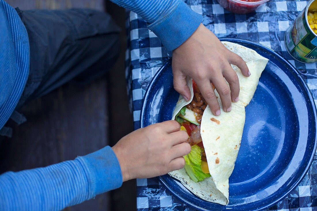 A child's hands rolling a filled burrito
