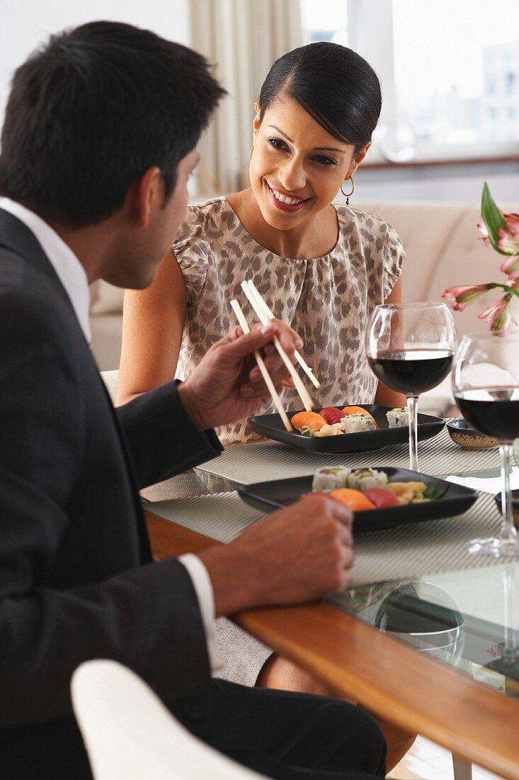 Elegant gekleidetes Paar beim Sushi-Essen