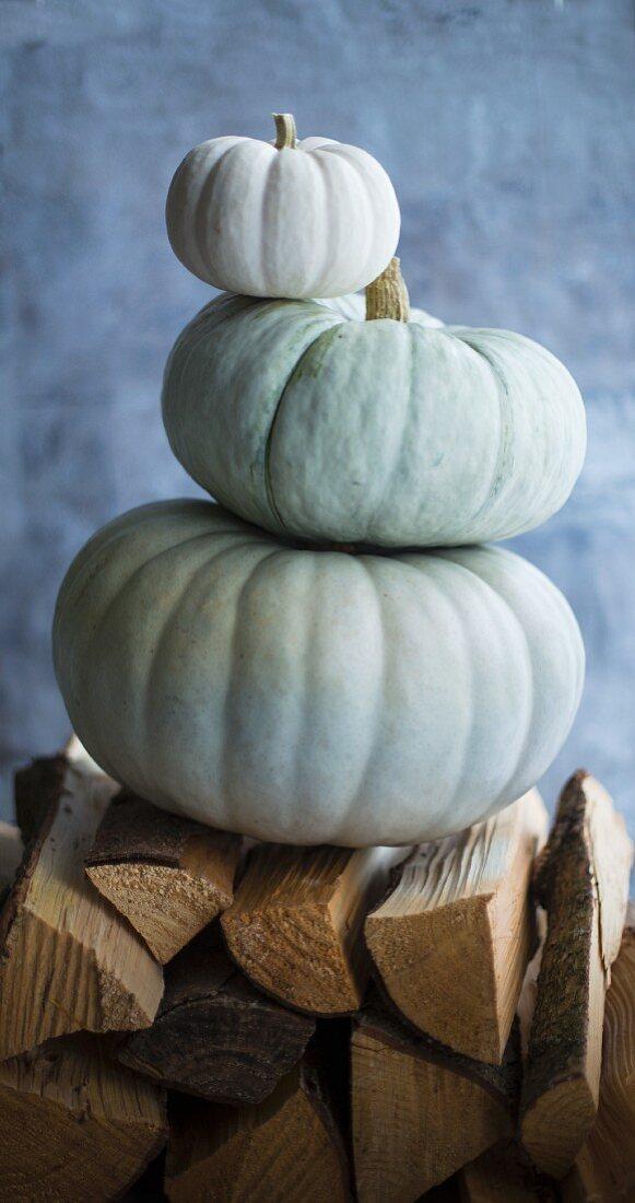 Three pumpkins, stacked on firewood