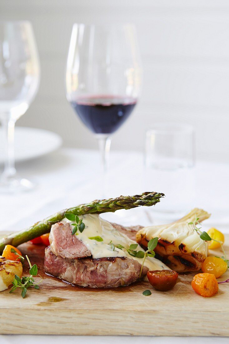 Ribeye steak with green asparagus, roasted tomatoes sauce and bearnaise
