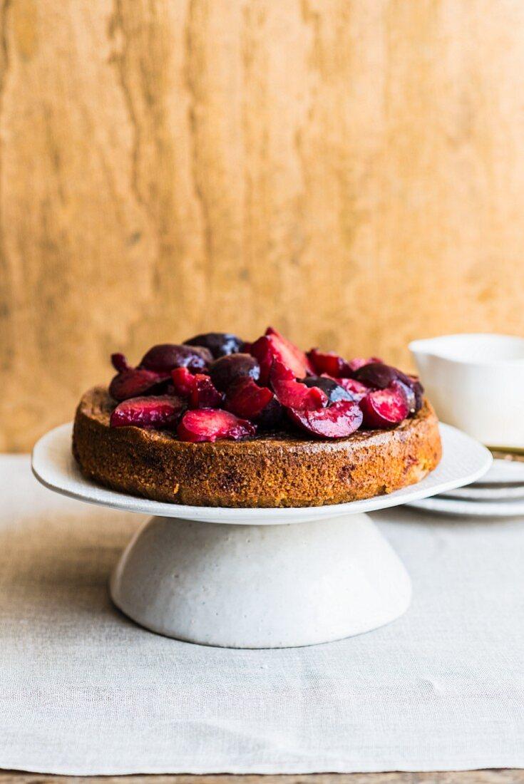 Hazelnut and plum cake on a cake stand