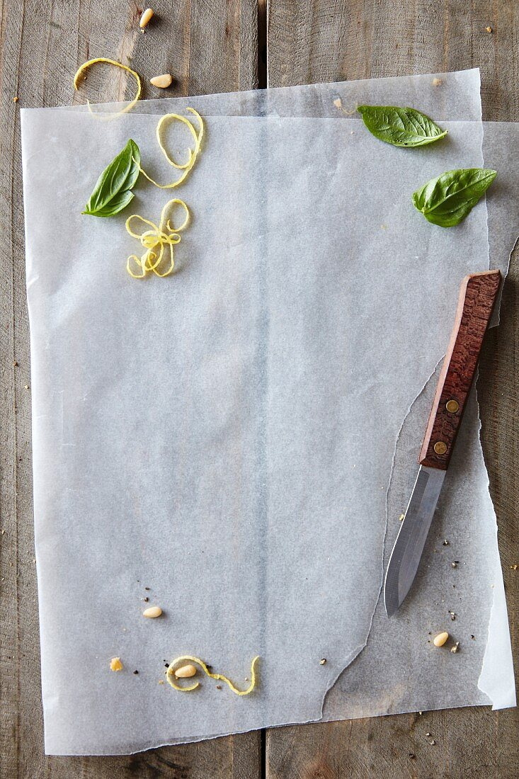 Backpapier, Zitronenzesten, Pinienkerne und Basilikumblätter auf rustikalem Holztisch