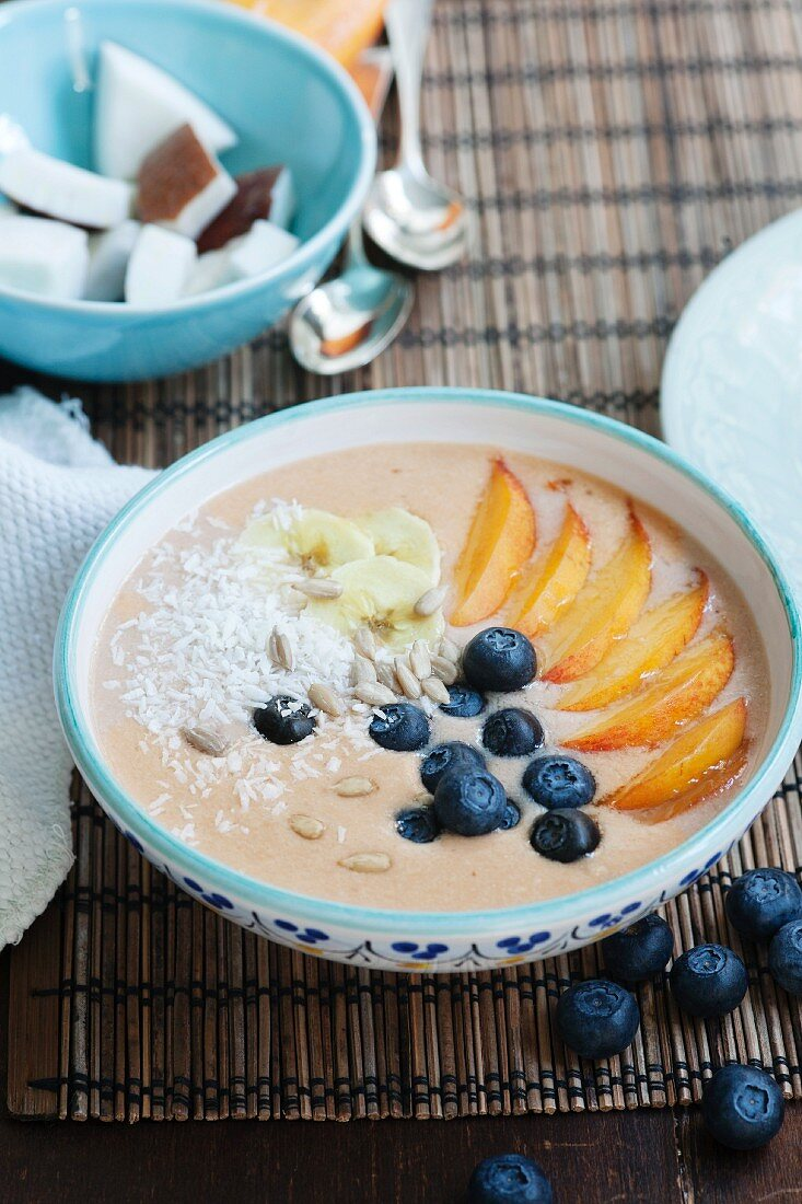 Smoothie bowl with peach, mango, banana, blueberries, coconut and sunflower seeds