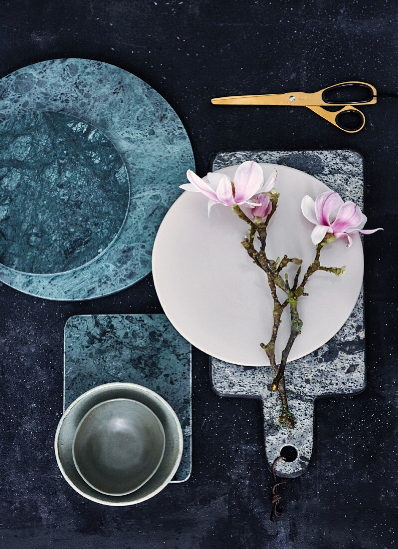 Green marble boards, ceramic dish and branches of flowering magnolia on marble board with leather strap