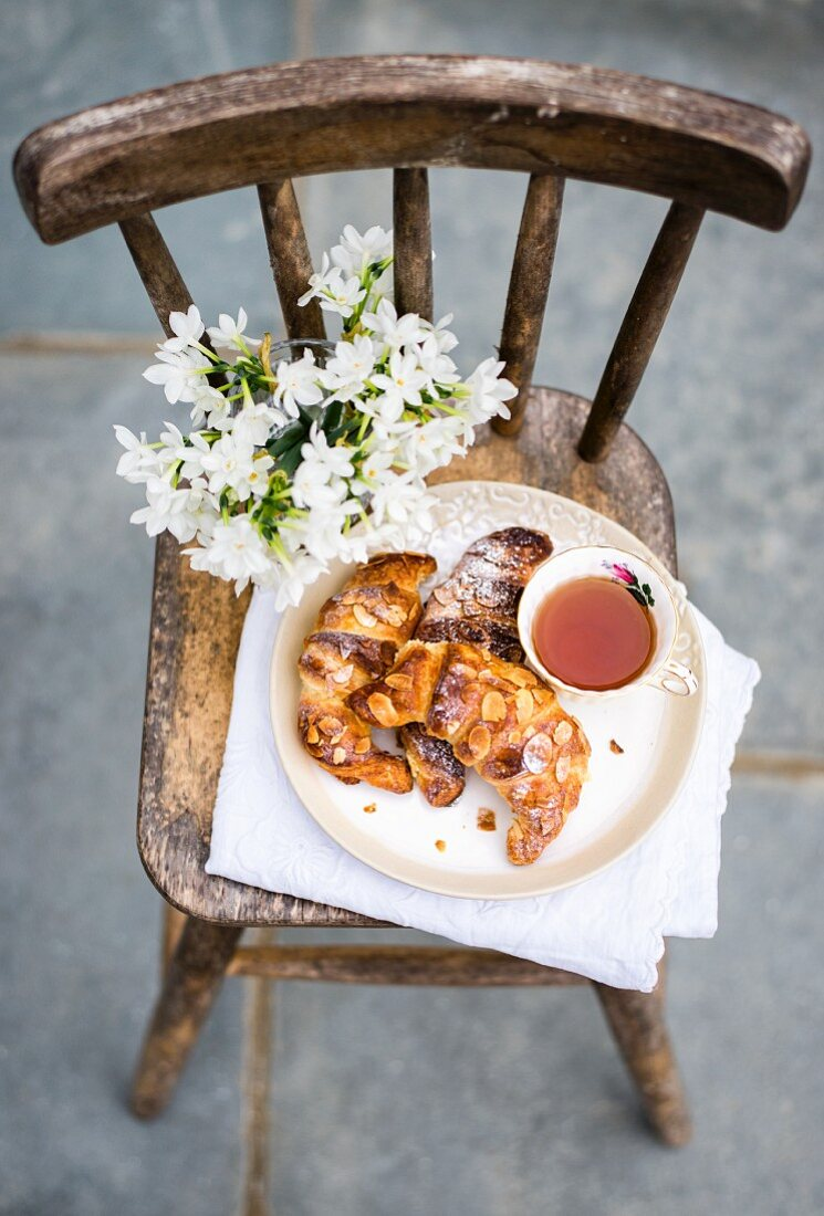 Homemade almond croissants with a cup of tea on rustic chair