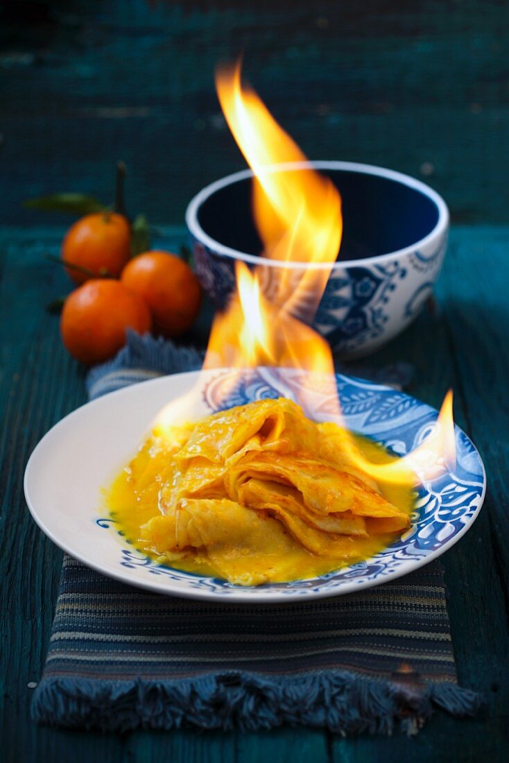 Crêpe Suzette being flambéed with orange syrup and orange liqueur