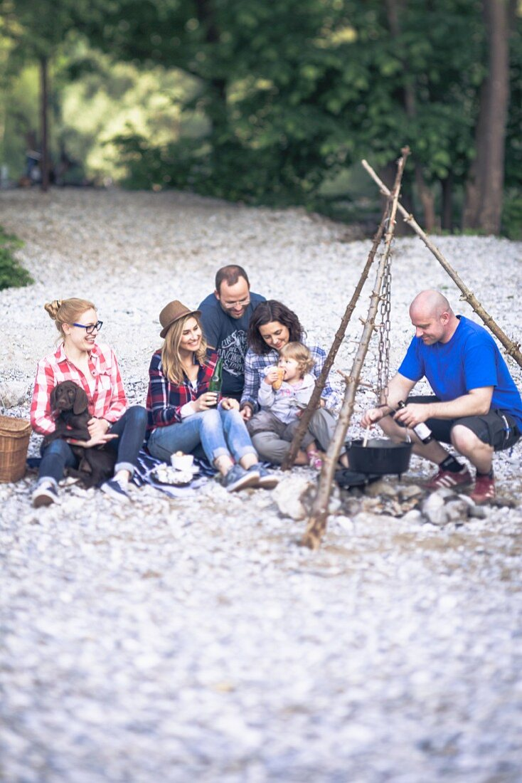 A family grilling on a river bank