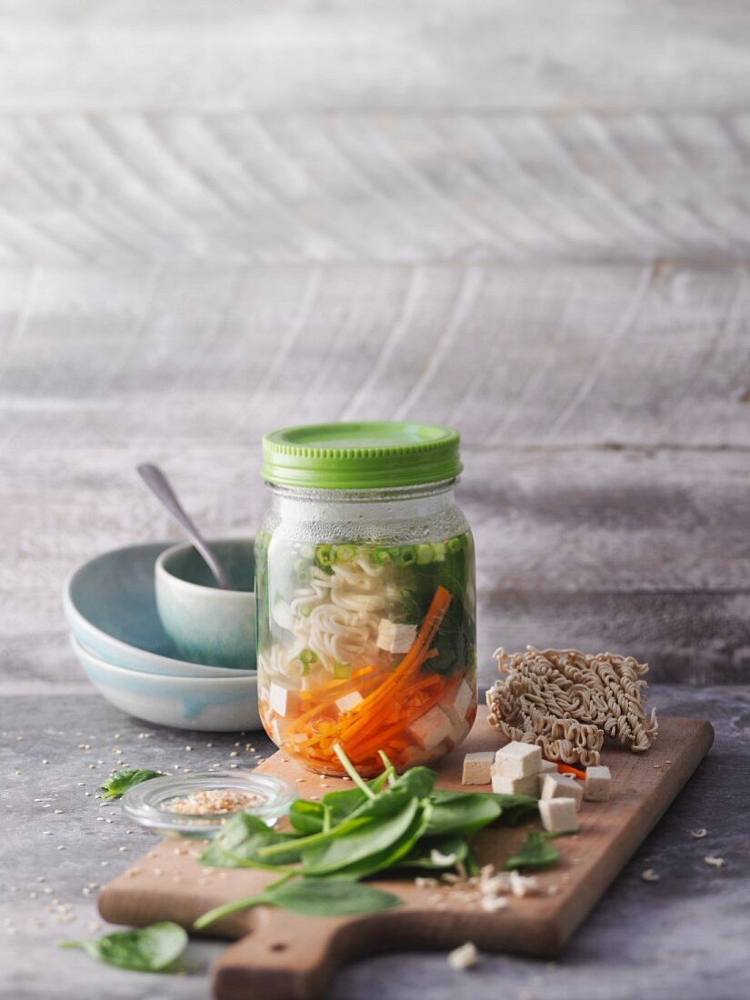 Oriental noodle soup with vegetables and tofu in a jar