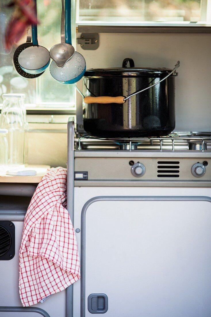 Saucepan on gas cooker in camper van