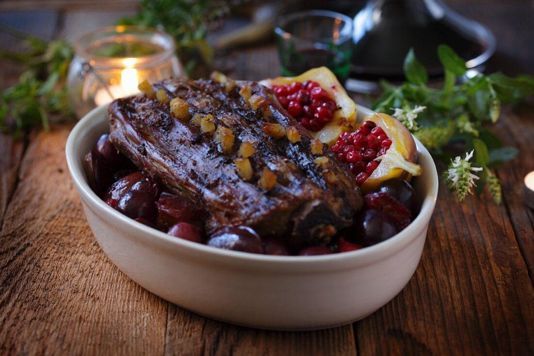 Studded roast venison with plums and lingonberry pears