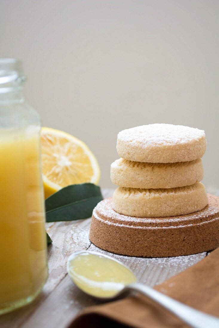 Lemon biscuits next to a jar of lemon curd