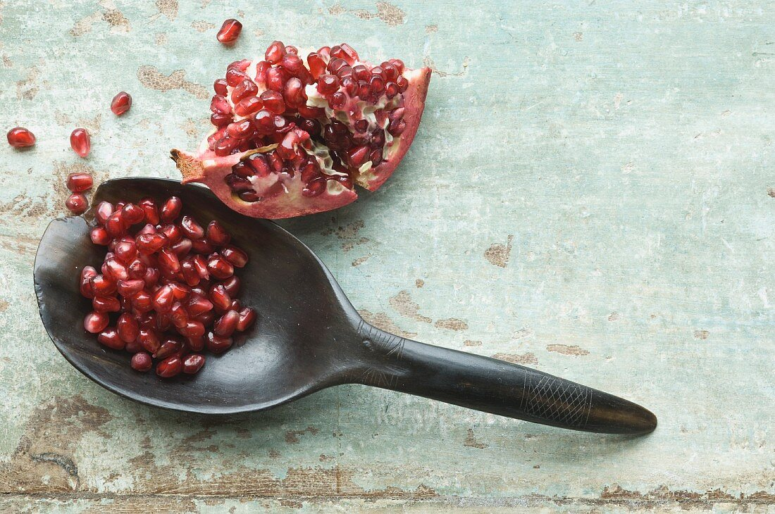 A pomegranate wedge and pomegranate seeds on a spoon
