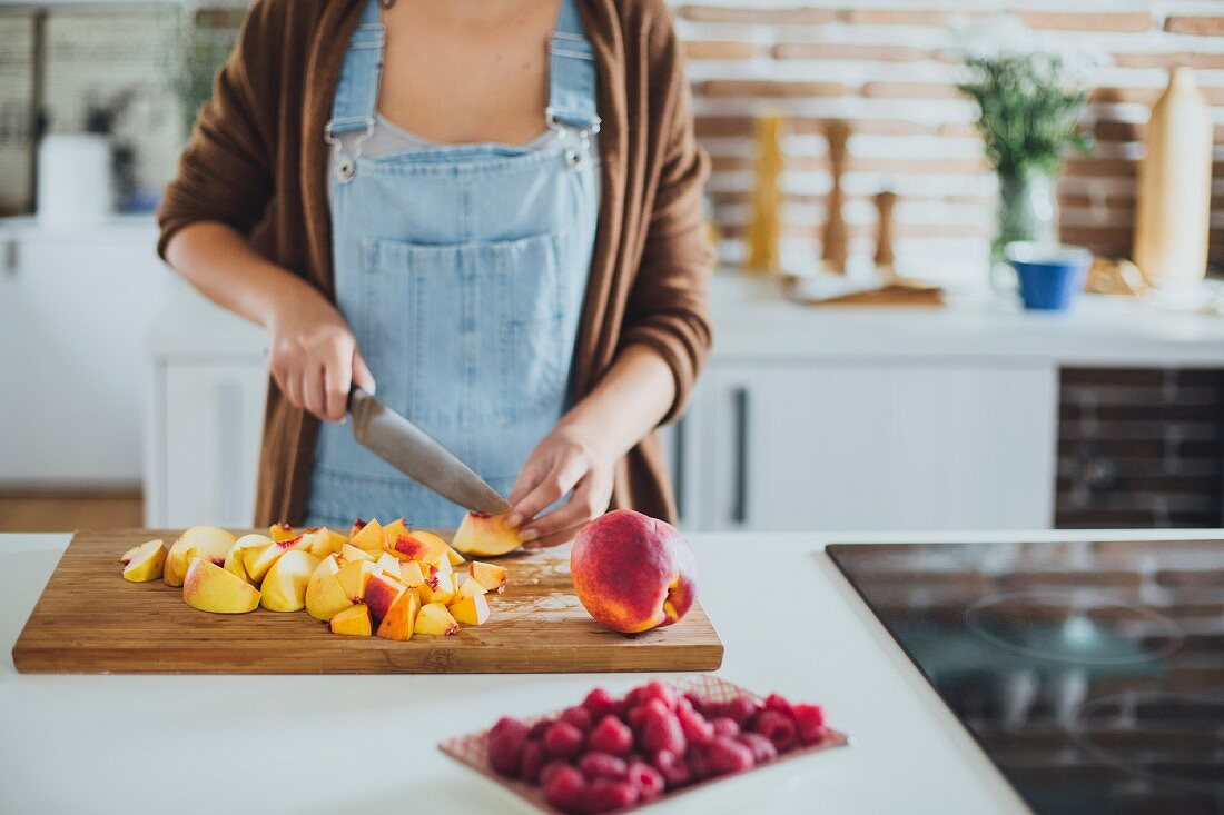 A woman cutting fruit on a wooden chopping board in a kitchen