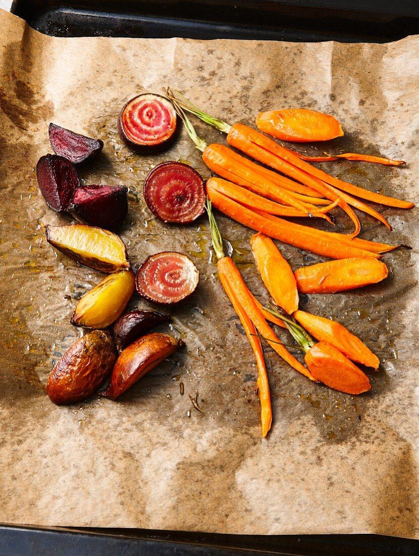 Vegan oven cooked vegetables (carrots, Jerusalem artichoke, Tonda di Chioggia) on baking paper