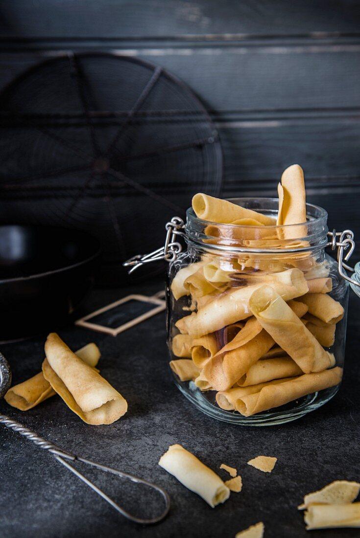 Freshly baked tuiles in a flip-top jar