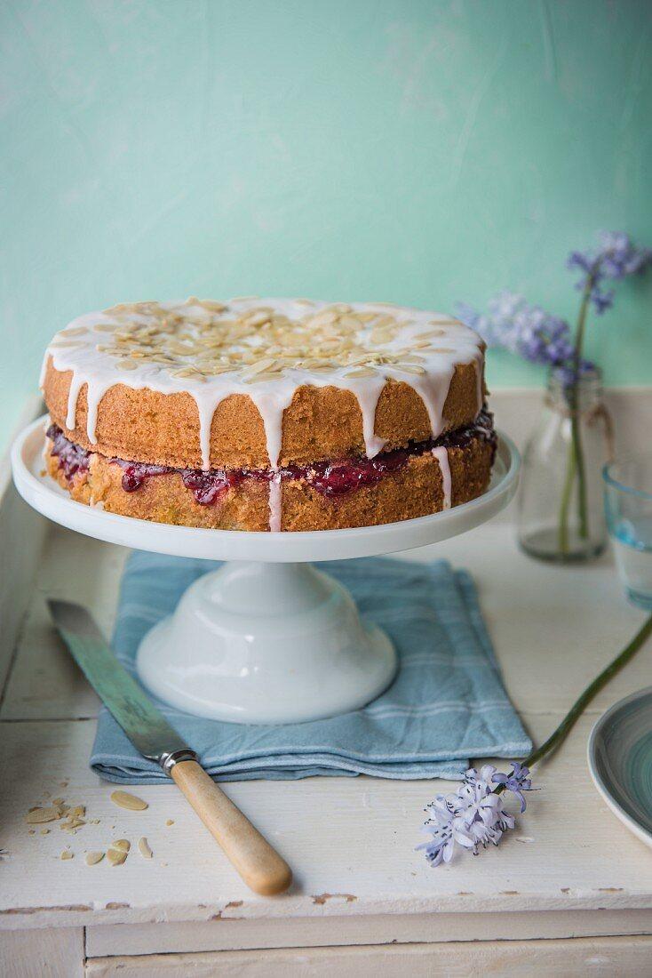 Almond sponge cake with cherry jam on the cake stand