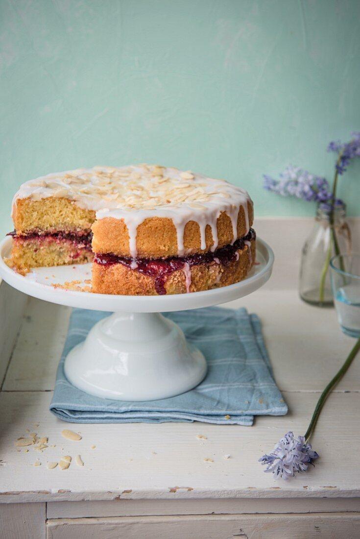 Almond sponge cake with cherry jam on a cake stand