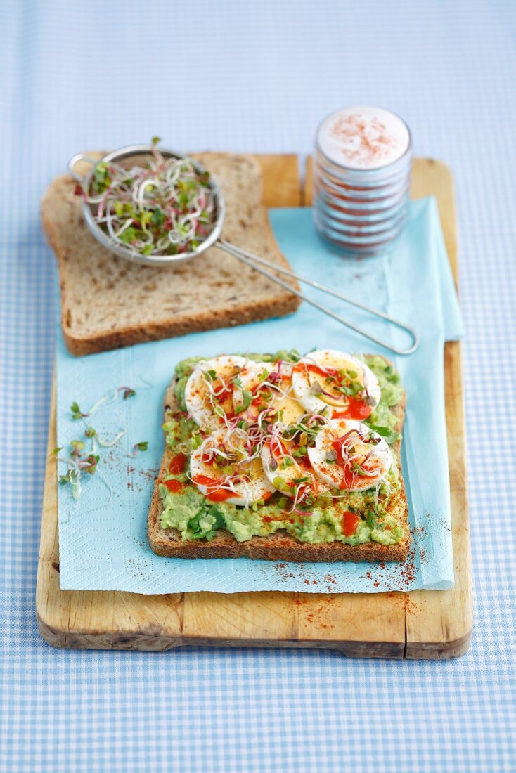 A sandwich with guacamole, hard-boiled egg, bean sprouts and sriracha sauce