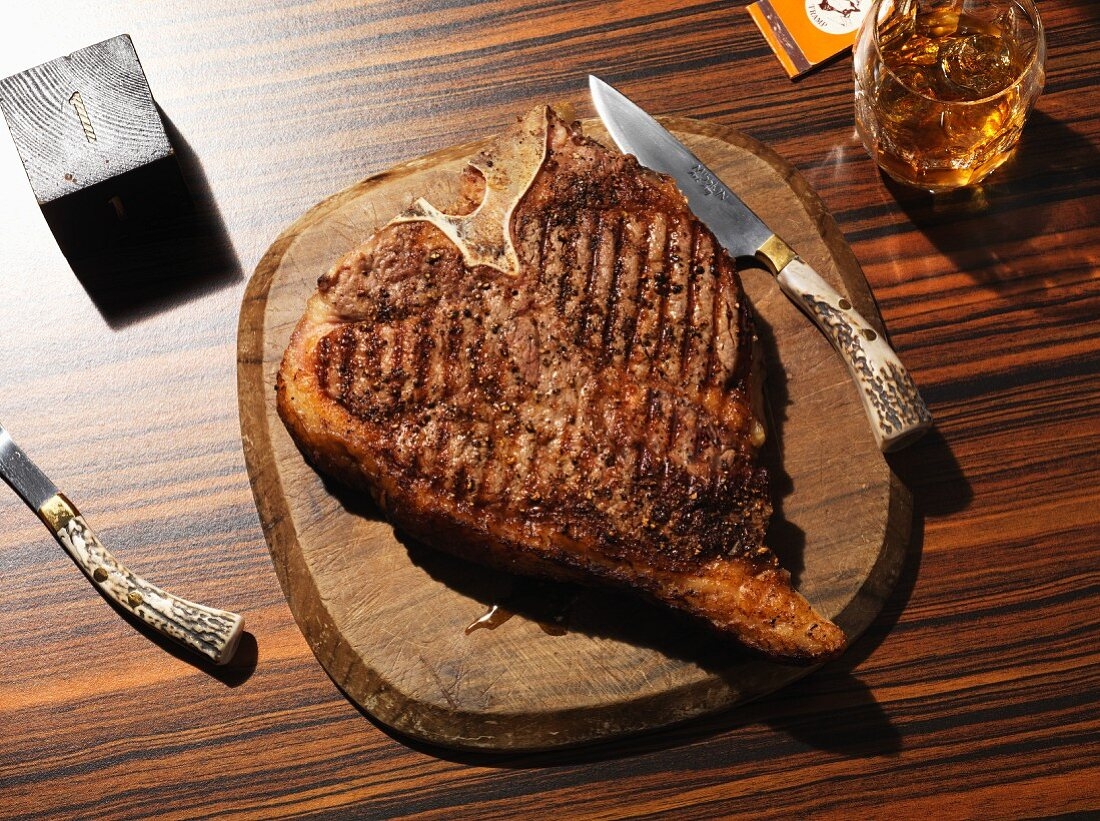 Grilled T-bone steak on a wooden plate with a steak knife