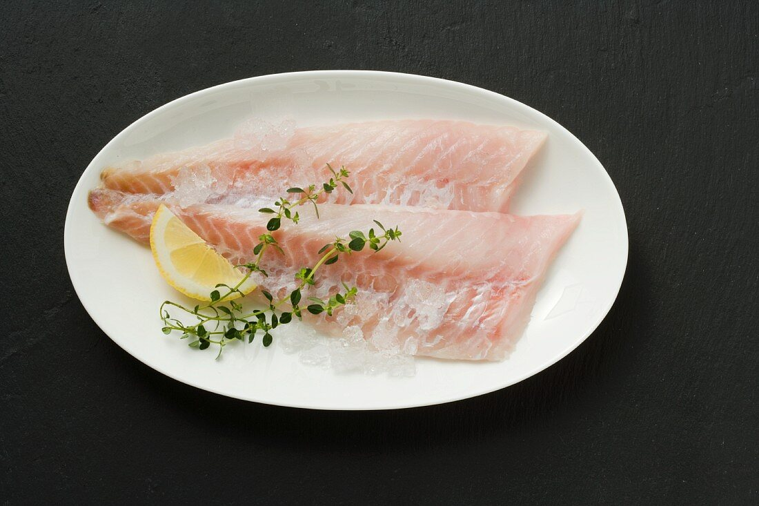 Rose fish fillets with lemon wedges and thyme