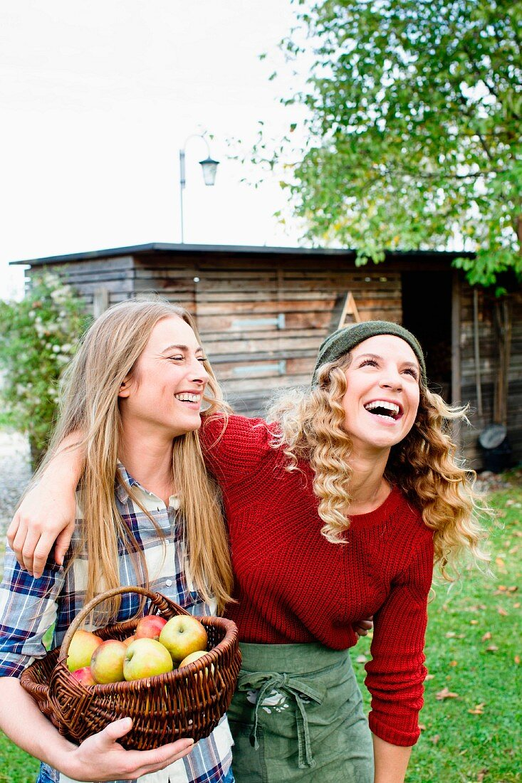 Smiling women in garden holding basket of freshly picked apples