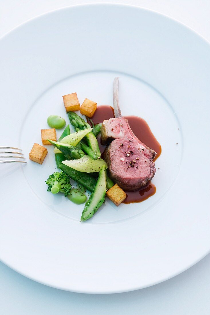 Rare lamb chop with green vegetables and diced potatoes