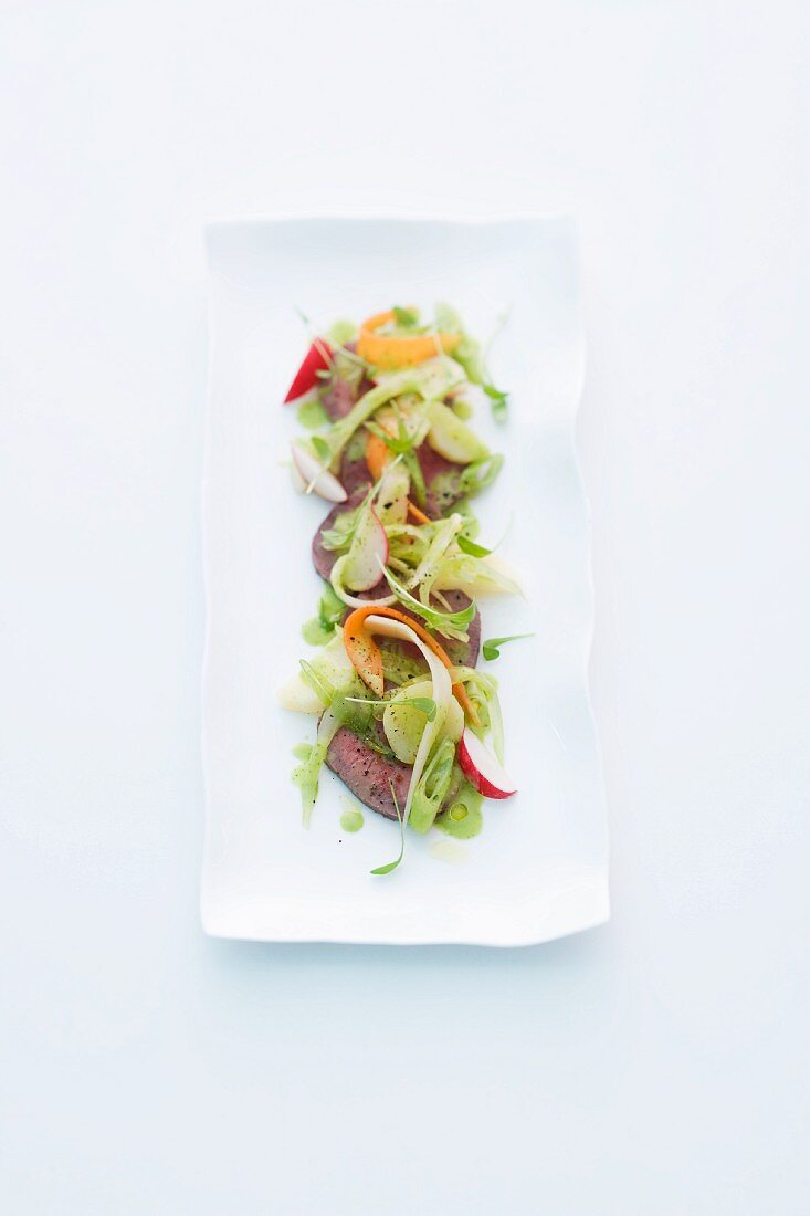 Poached beef fillet with a warm vegetable salad
