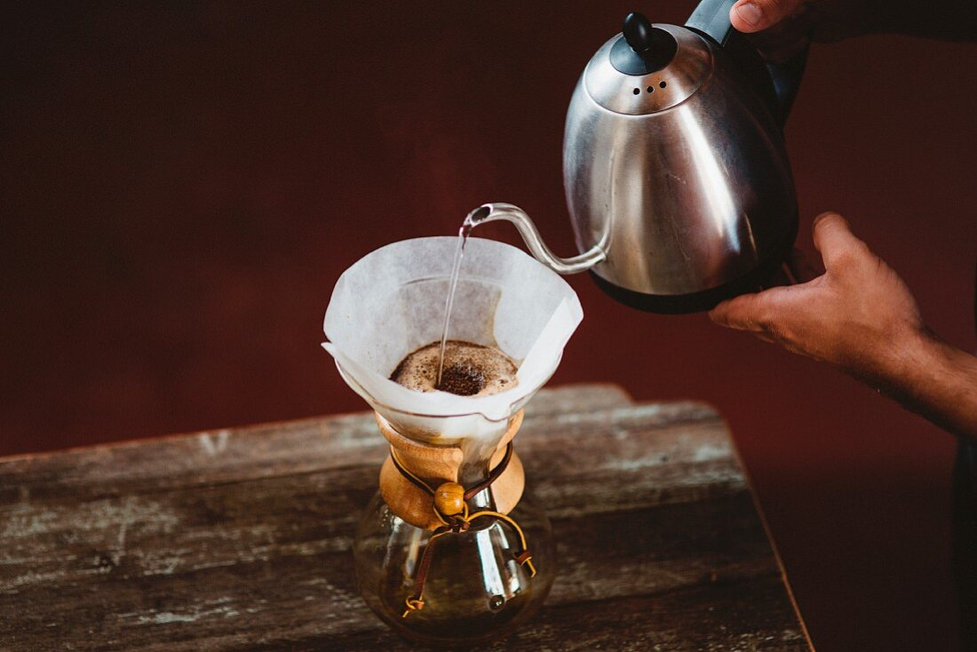 Person pouring water through a coffee filter in a Chemex coffee carafe