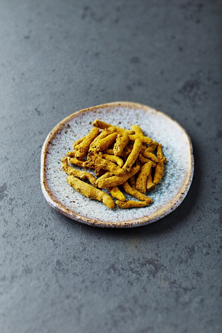 Organic turmeric roots on a ceramic plate