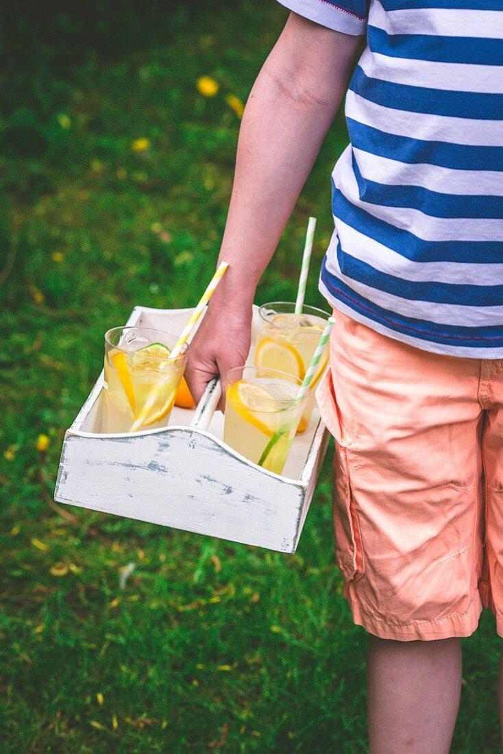 A boy carrying lemonade glasses on a tray
