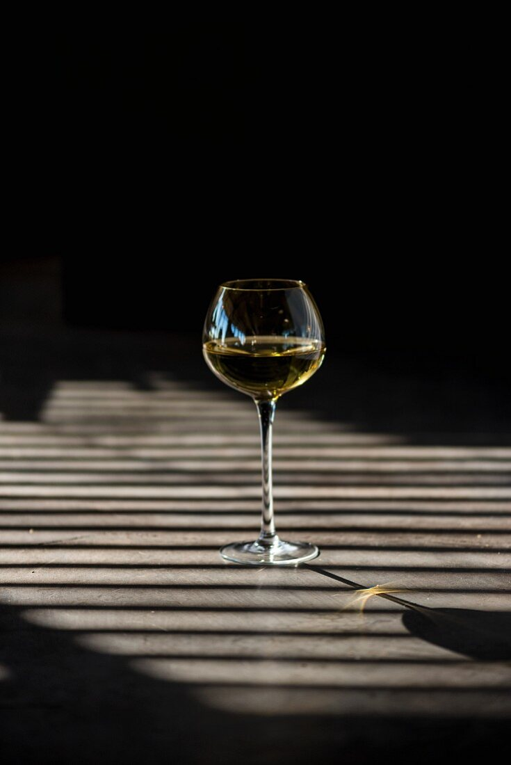 Shadows playing over a glass of white wine