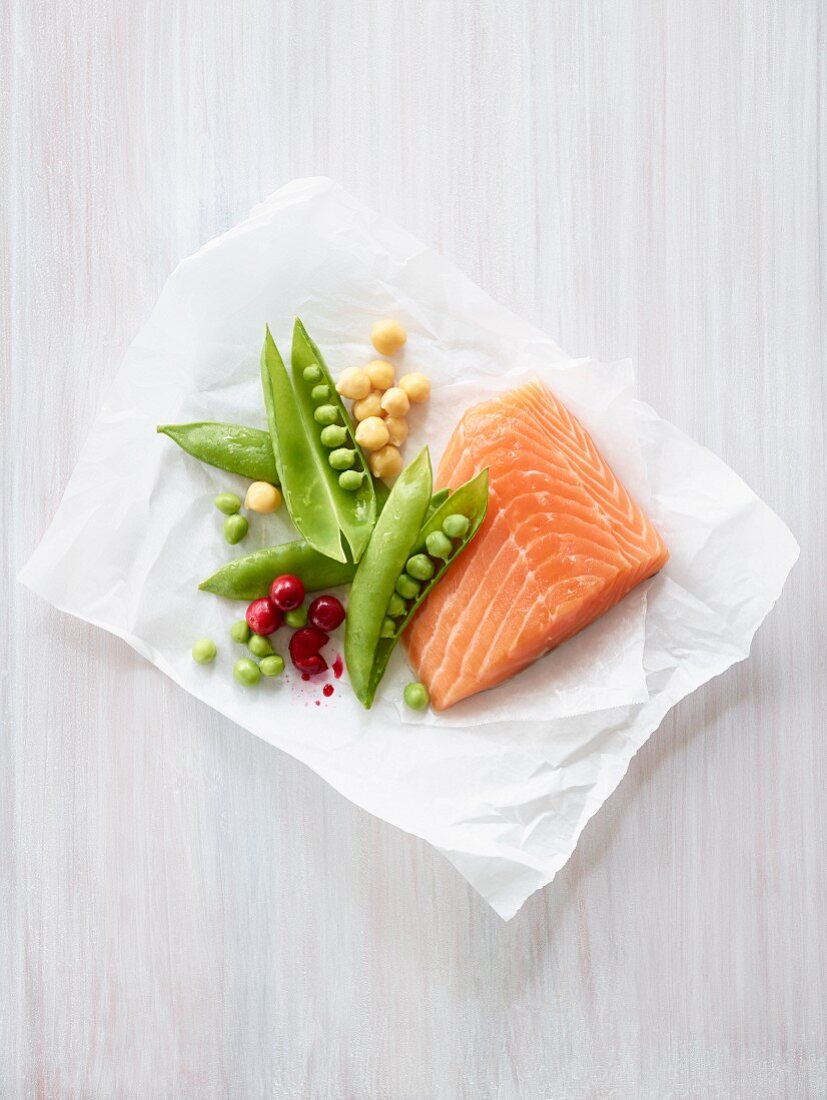 Salmon fillet with peas, chickpeas and cranberries on a piece of paper