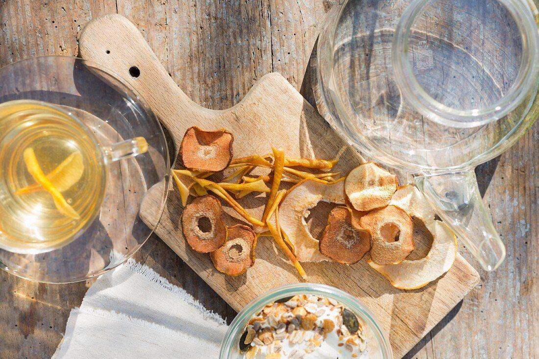 Getrocknete Quittenscheiben und ?schalen auf altem Holzbrett, Quittentee und Joghurtmüsli
