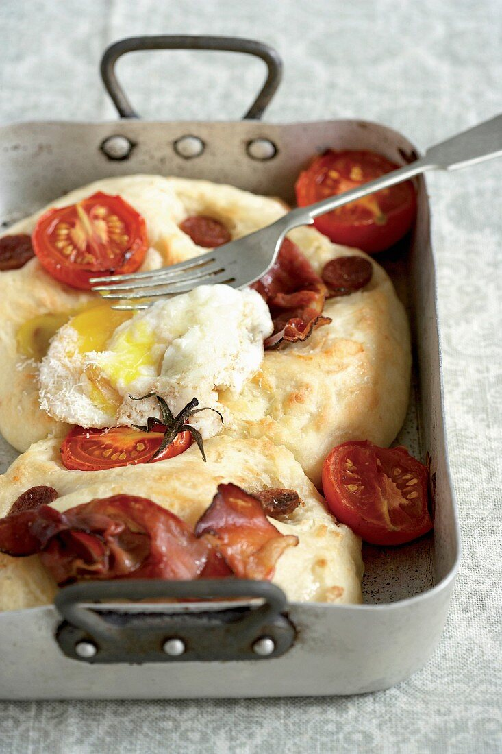 Focaccia with ham, sausage, tomatoes and a poached egg