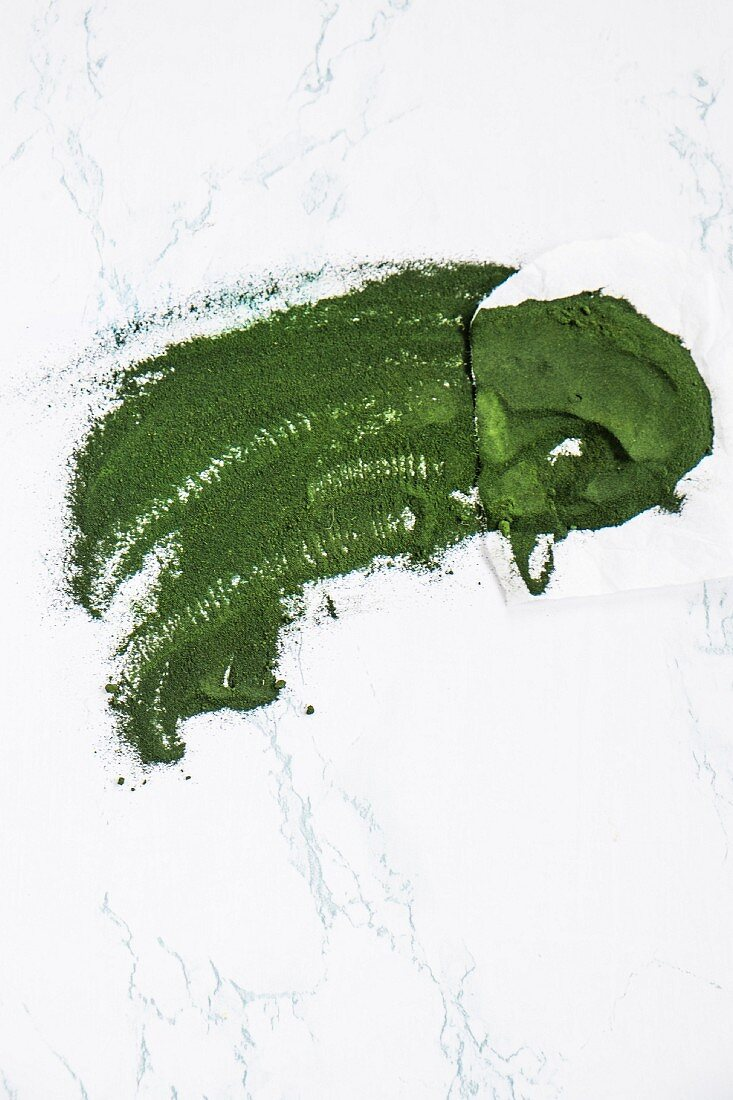 Chlorella and algae powder on a marble background