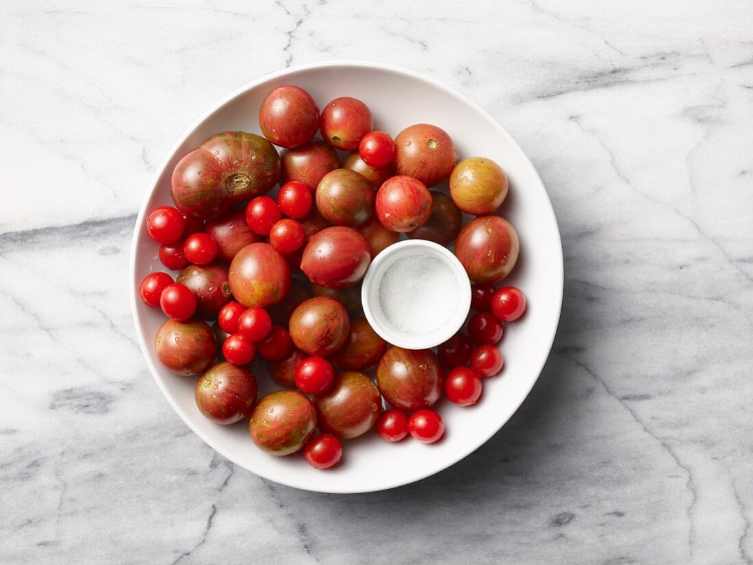 Various tomatoes with a bowl of salt