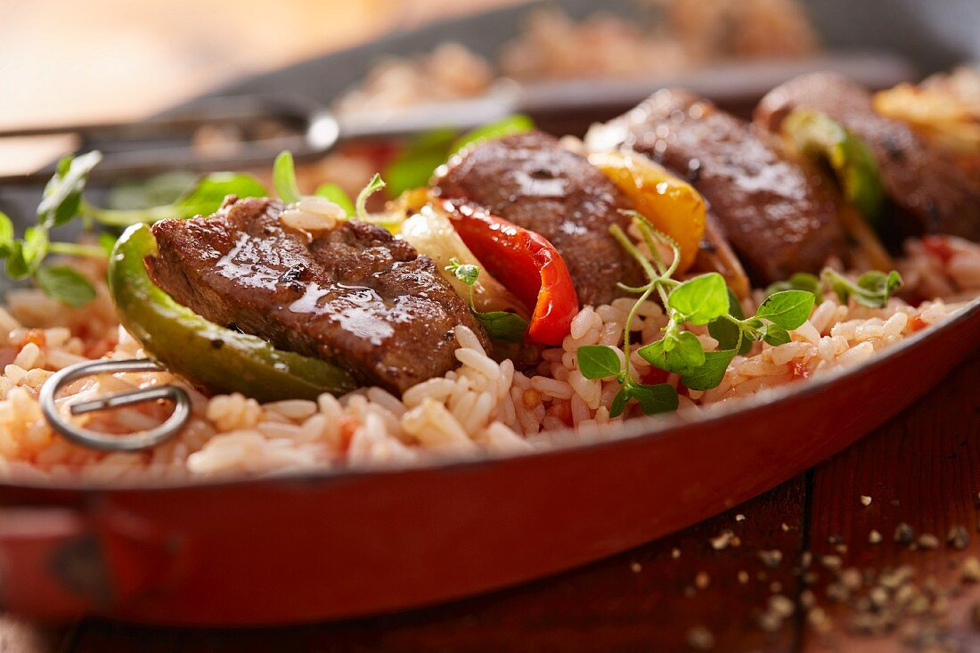 A lamb kebab with peppers on a bed of rice