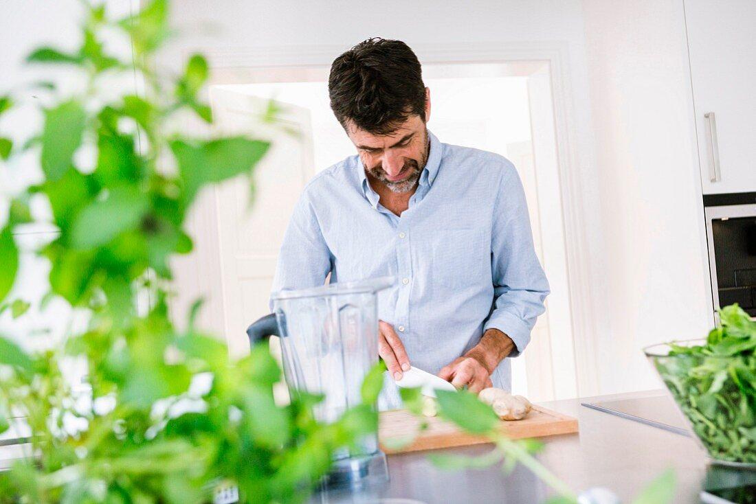Mann schneidet Ingwer in der Küche